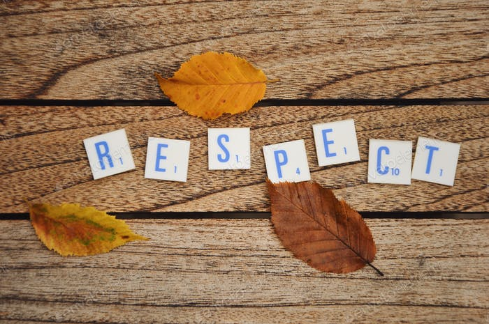 Overhead photo of letters or text saying respect and autumn leaves on a wooden tabble