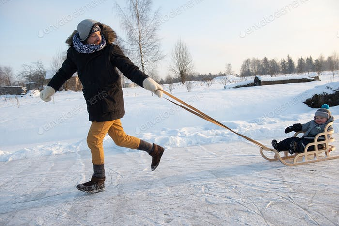 Padre está tirando niño en trineo caminando en el día helado de invierno al aire libre. Hermosa luz solar de la noche.