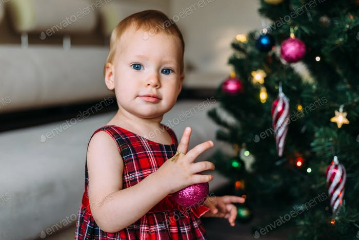 Little cute girl near a decorated Christmas tree. Concept of Christmas and New Year.