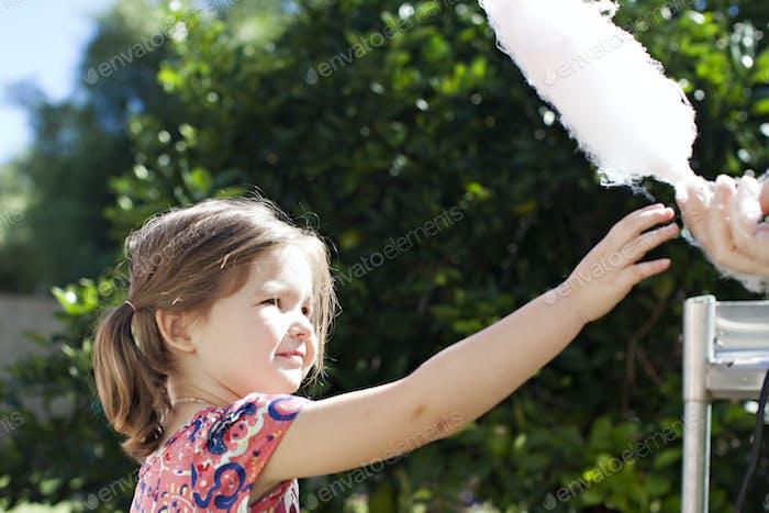 Kleines Mädchen, das auf einer Messe im Sommer nach Zuckerwatte streckt