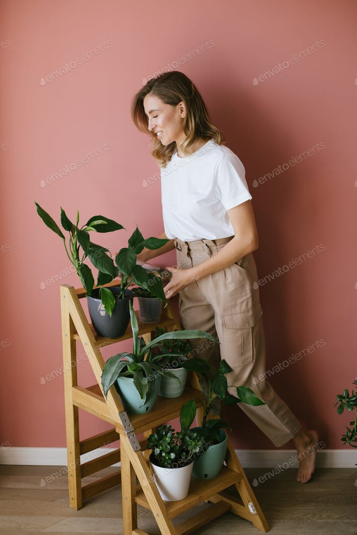 Young woman taking care of home plants and greens