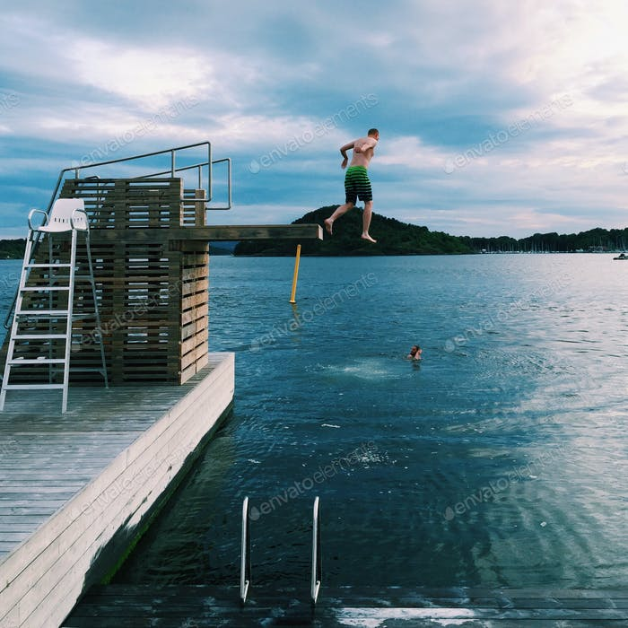 Guys jumping in the bay from a diving board