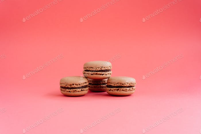 Macarons isolated on pink background with copyspace.