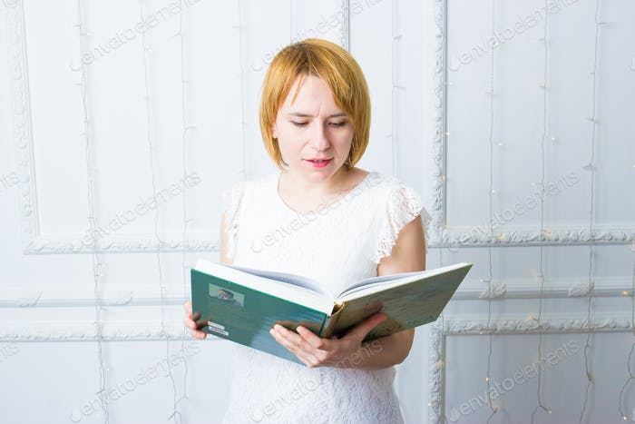 Girl in white with book. Reading.
