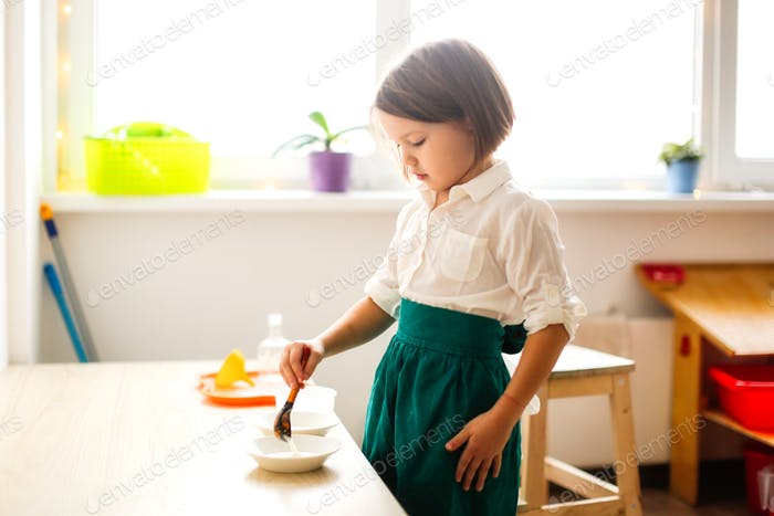 kid girl in a linen apron plays with bulk cereals, developing sensory activities