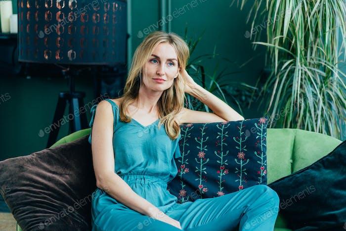 joven atractiva de treinta años de edad, mujer rubia está descansando en el sofá, apoyándose en su brazo en el pensamiento.