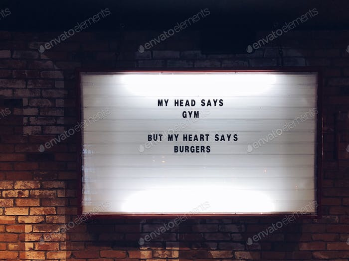 My head says gym, but my heart says burgers. A white glowing sign on a brick wall