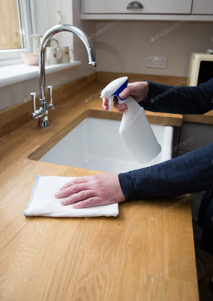 A housewife deep cleaning during the Coronavirus outbreak with disinfectant