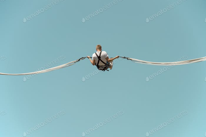Man on blue sky background elastic rope jumping