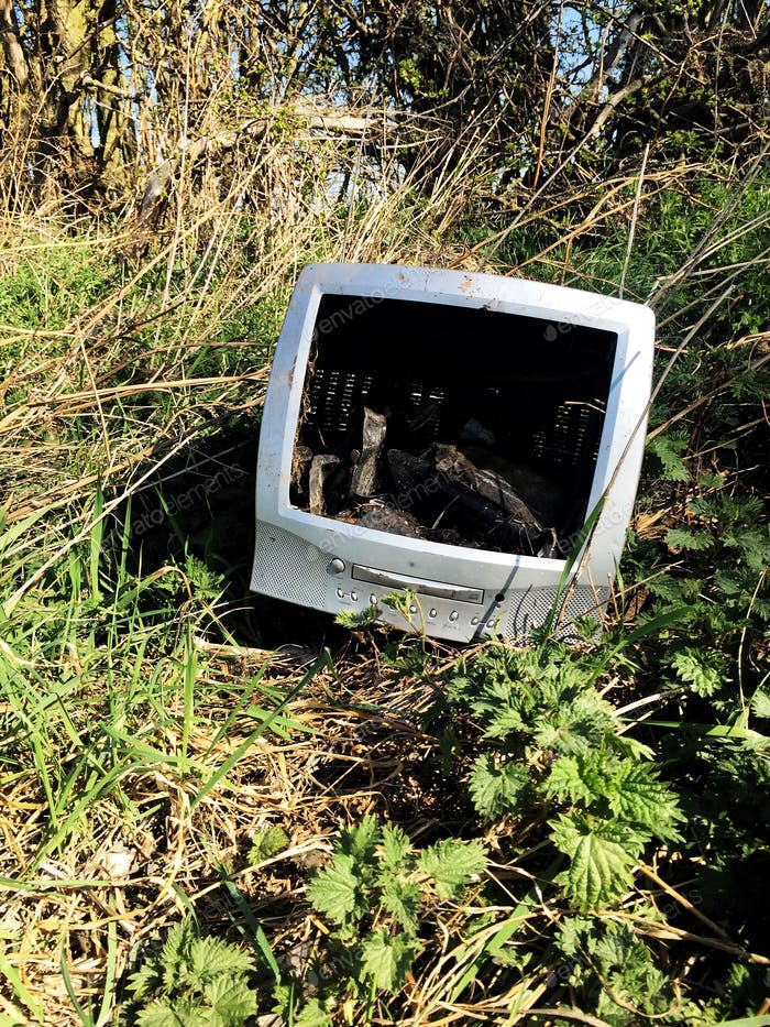 old technology out of date computer, TV dumped in wasteland in a fly tipping concept with copy space