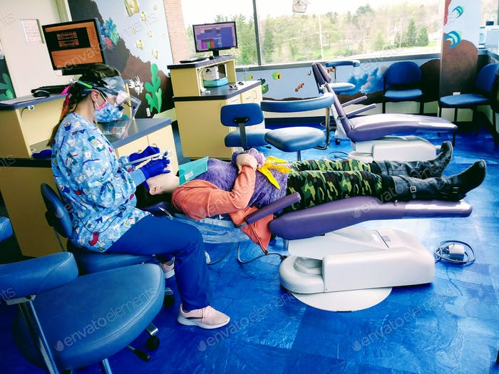 A medically trained dental assistant cleaning a teenager