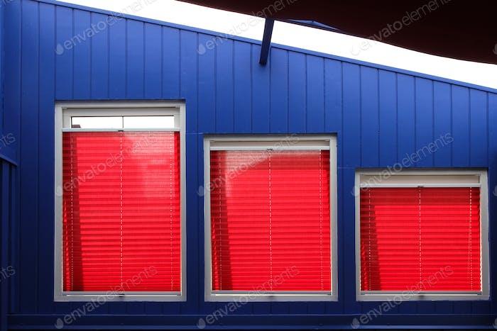 Home Interior Design. gewagt mit leuchtend roten Jalousien in drei unterschiedlich großen Fenstern in einer Reihe