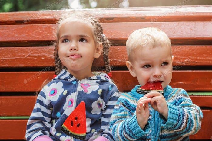 Two adorable kids, brother and sister, eating bright red candies with watermelon taste sitting on th