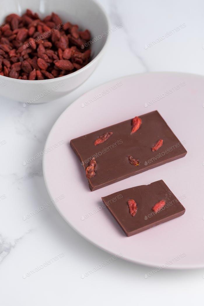 Handgemachte gesunde rohe Goji-Beere Schokoladenriegel und Goji-Beeren in Schüssel.