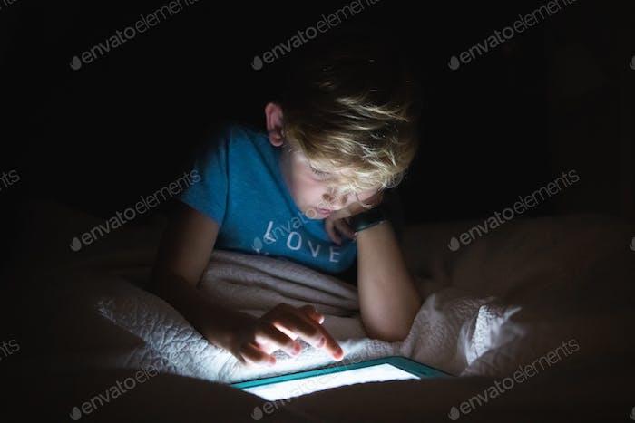 Boy using tablet computer in the dark