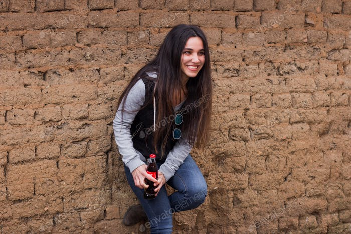 A woman holds Coca-Cola bottle and smiling, bricks wall background