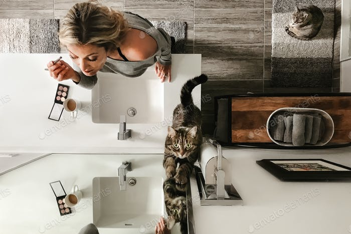 Woman getting ready for the day with her cats
