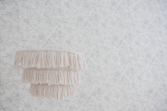 On a gray minimalist background, a macrame lamp, made by hand. Scandinavian, modern, trendy interior