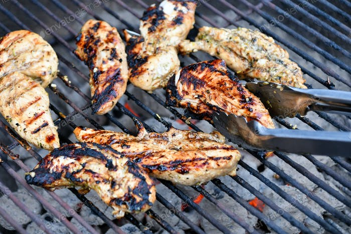 Cooking marinated chicken tenders strips over charcoal briskets on a hot grill using tongs to turn