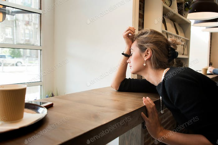 Tired girl in the café, sitting alone, missing