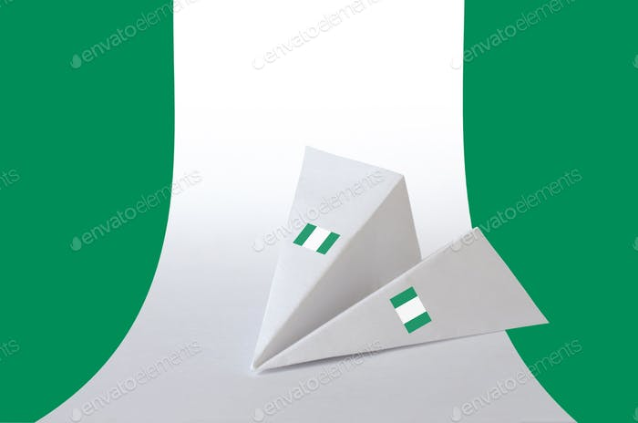 Nigeria flag depicted on paper origami airplane. Oriental handmade arts concept