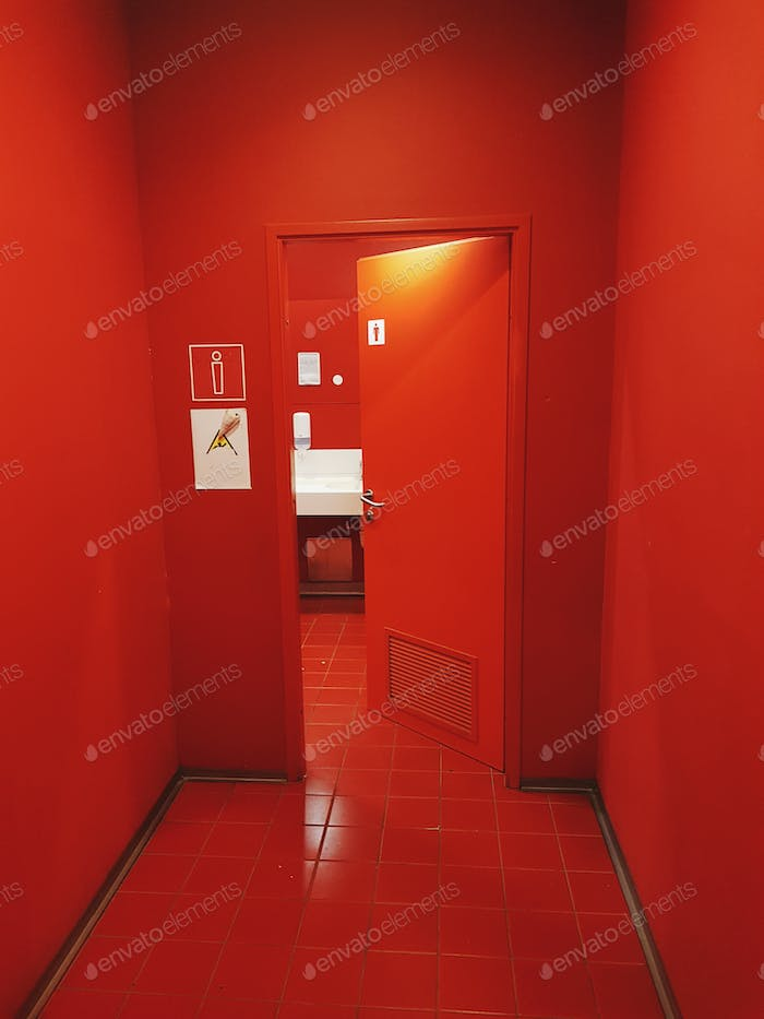 📷nominated📷A red hallway with a red door. Entrance to a toilette.