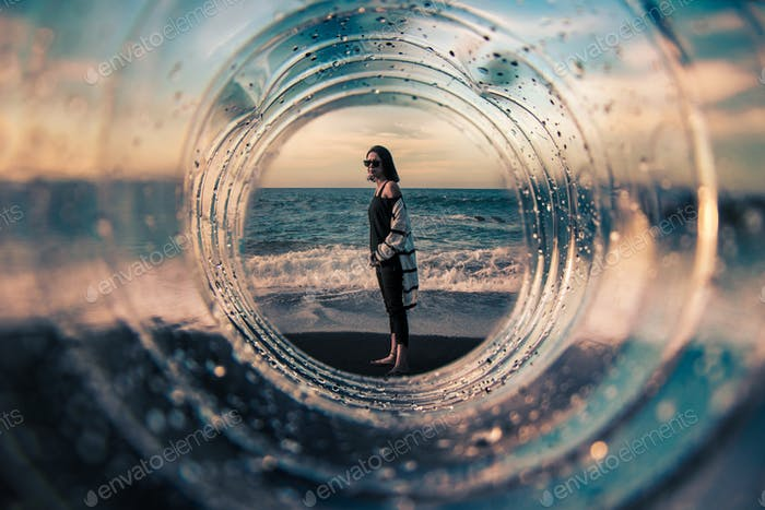 Composition with a girl on the beach photographed through a transparent tunnel, with a focus on the