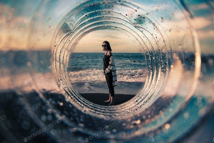 Композиция с девушкой на пляже сфотографирована через прозрачный туннель, с акцентом на