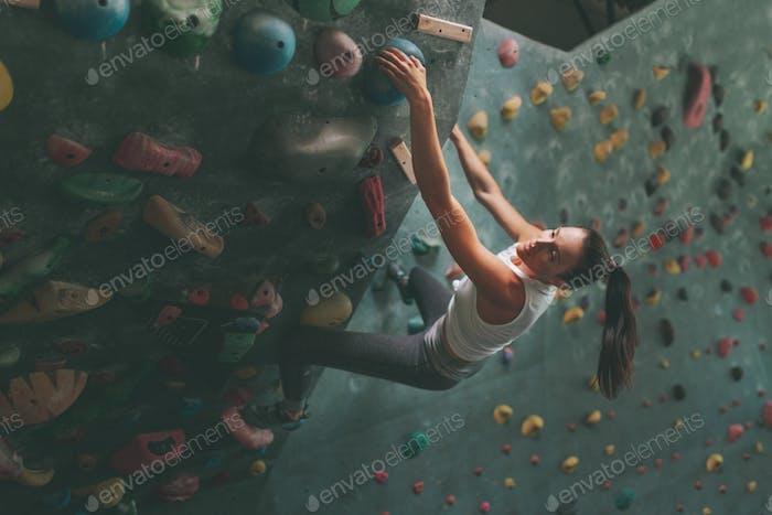 A woman climbing a climbing wall at an indoor gym.