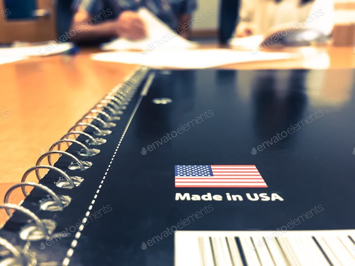 Notebook on the table, made in USA,selective focus . People  in the background