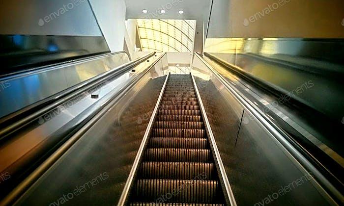 Vanishing point of escalator going up toward light.