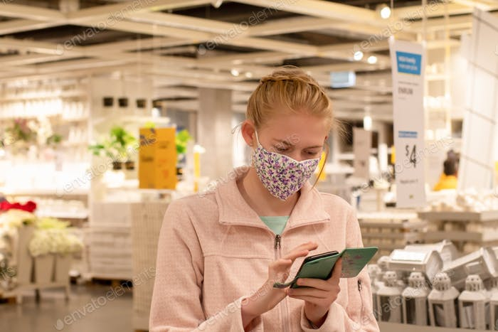 Girl wearing face mask with mobile phone at the IKEA store. Covid-19 outbreak. Mandatory face masks