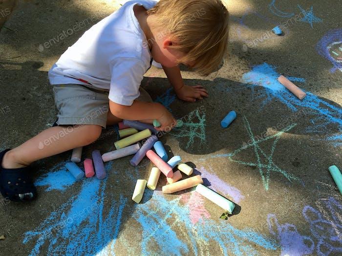 Kleinkind spielt mit Gehsteig Kreide