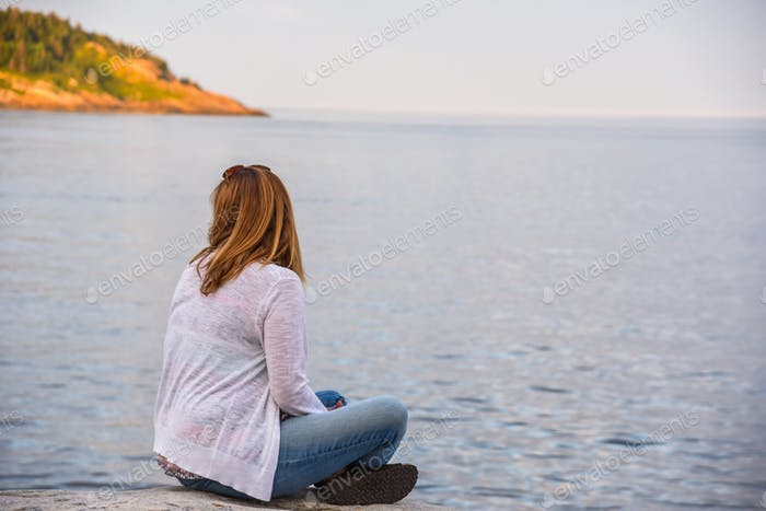 Woman in jeans and white sweater sitting on rocky shoreline in Tadoussac