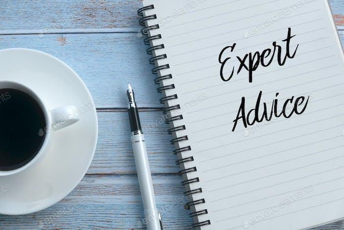 Draufsicht einer Tasse Kaffee, Stift und Notizbuch geschrieben mit Expert Advice auf hölzernen Hintergrund