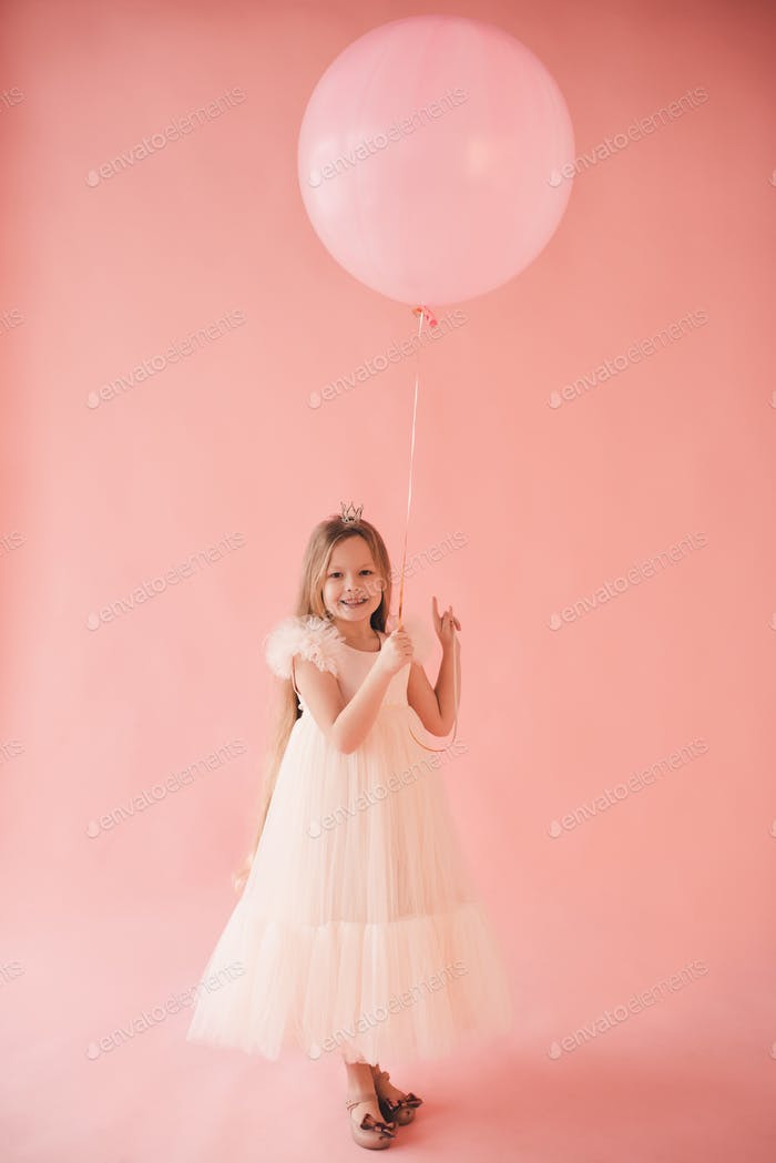 Smiling child girl 7-8 year old wearing trendy dress hold big balloon over pink background.