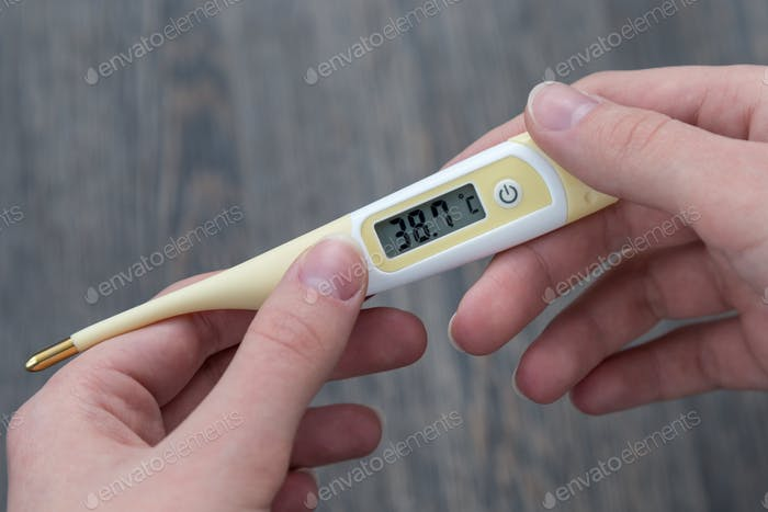 thermometer with high temperature in hands
