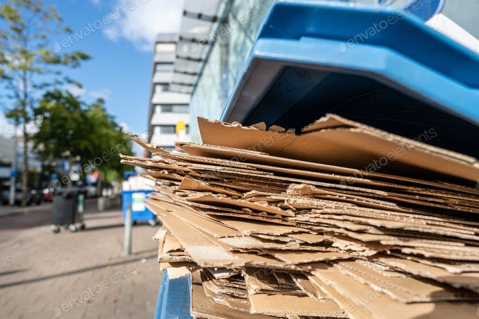 Used cardboard boxes to be collected in a plastic container for paper waste separation recycling.