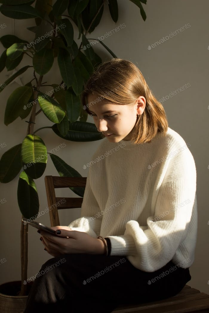 beautiful teenage girl chatting on social media sitting in her room on a sunny morning