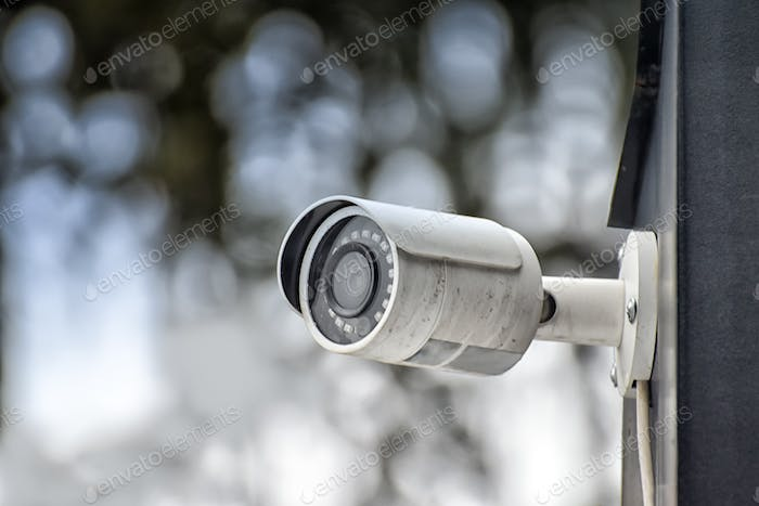 Security system of outdoor video surveillance, CCTV Security Camera on blurred outdoors background.