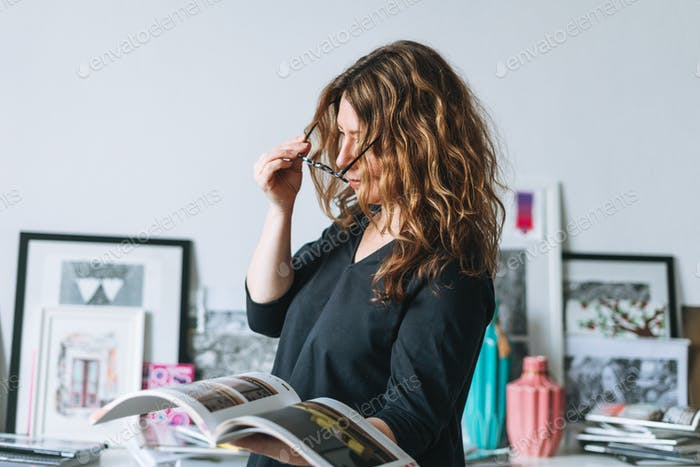 Woman in glasses with magazine