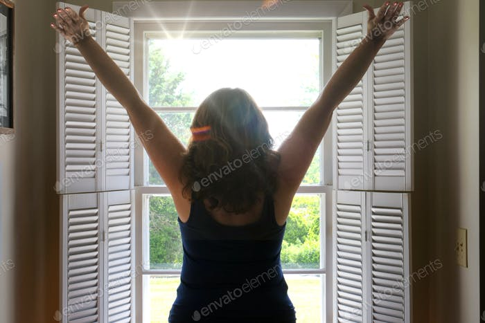Good morning!! Woman with outstretched arms throwing open the blinds, greeting morning new day sun