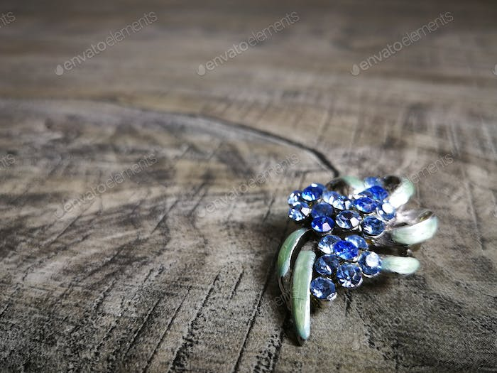 Brooch in blue gemstone for clothes isolated on wooden background.
