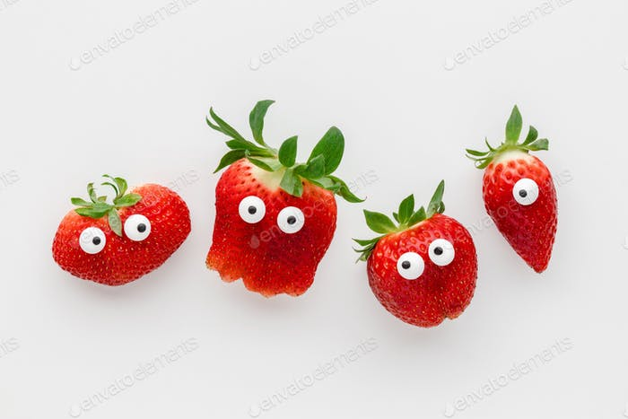 Funny faces strawberries on a white background