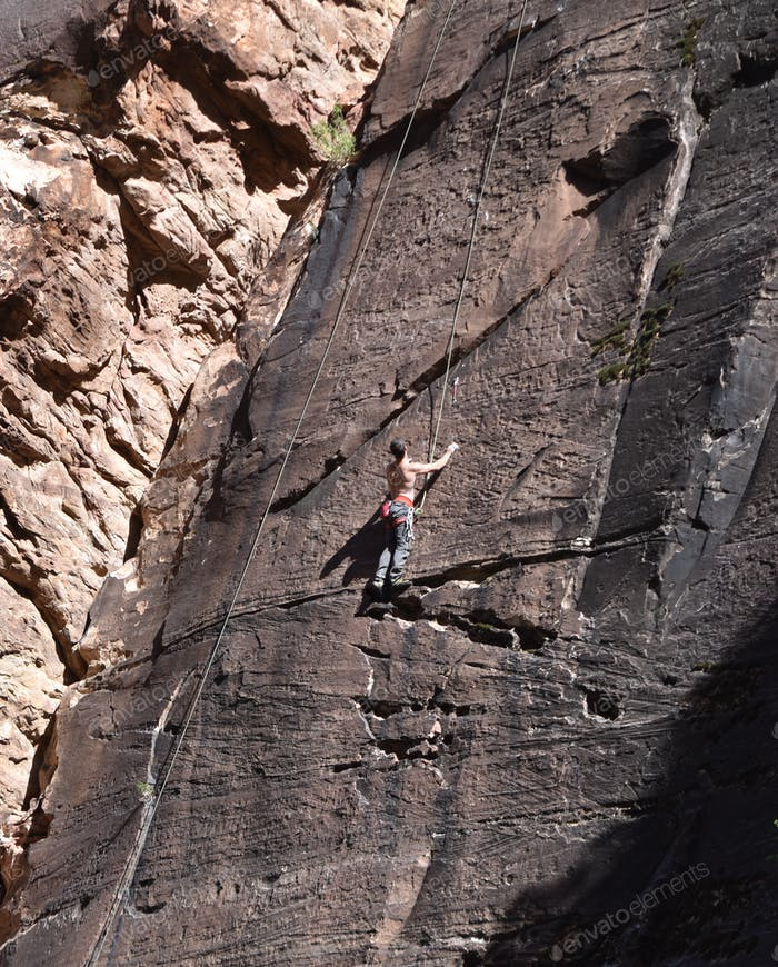 Hey serious climber on a sheer rock. Making a difficult climb determination