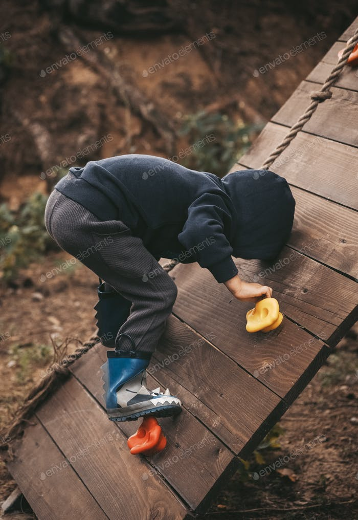 little boy climbing the wall in the playground