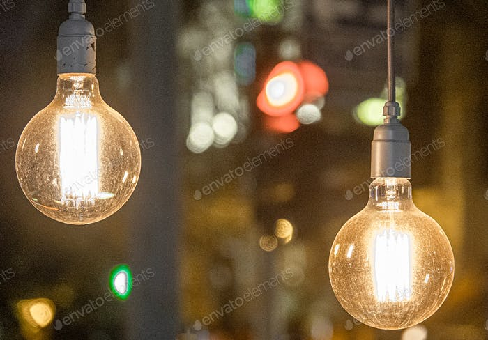 Beautiful vintage and retro light bulbs hanging decor glowing with bokeh lights at the background.