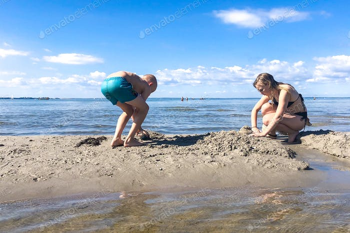 Siblings digging in the sand at the beach
