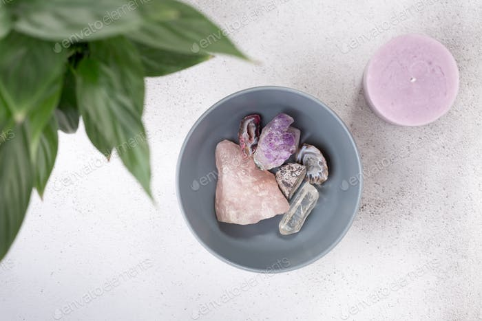 Aerial view of quartz and amethyst crystals in a bowl with plant and candle.