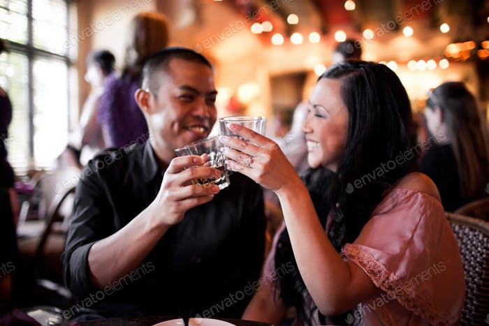 Ein junges Paar genießt Cocktails während der Happy Hour.